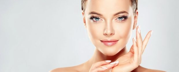 Beautiful Young Woman with Clean Fresh Skin touch own face . Facial treatment . Cosmetology , beauty and spa